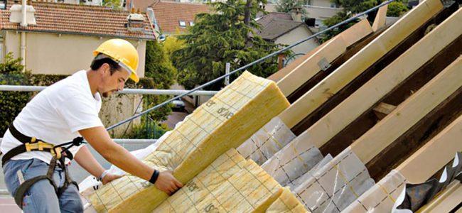 Werkman brengt isolatie aan op dak.