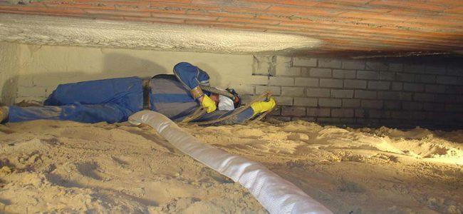 Een man ligt in de kruipkelder isolatie aan te brengen.