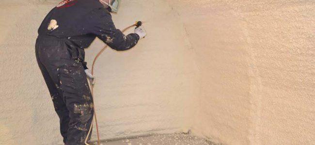 Een man is bezig met de kelder te isoleren.