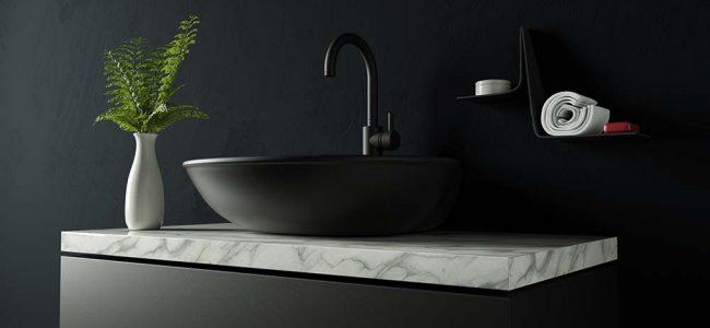 Zwarte lavabo op marmeren blad.