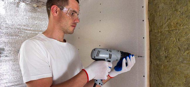 Een werkman is gyprocplaten aan het monteren.