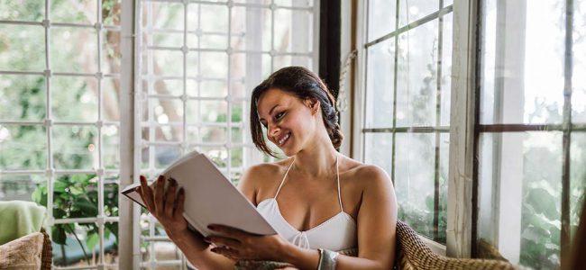 Vrouw die boek leest in veranda.
