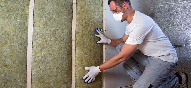 Een man plaatst isolatieplaten.