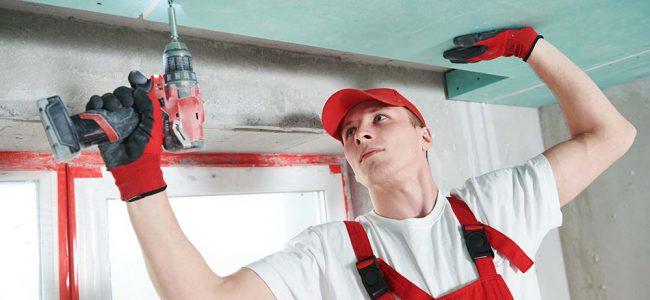 Een werker is platen in het plafond aan het monteren.