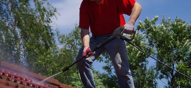 Man reinigt dak met hoge druk