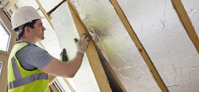 Een werkman brengt isolatieplaten aan in het dak.