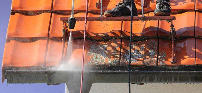 Hoogtewerker reinigt dak