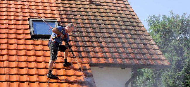 Man op dak die dak kuist.