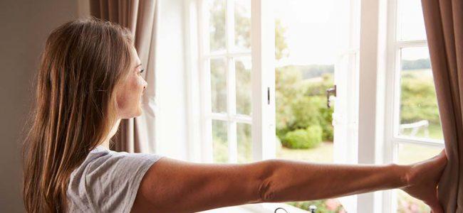 Vrouw kijkt door raam met gordijnen.