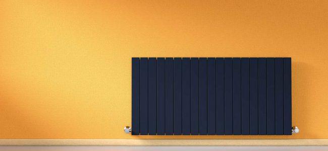 Zwarte radiator op oranje muur