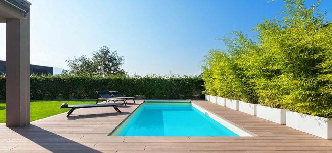 Zwembad in tuin met ligzetels