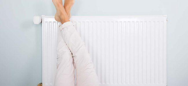 Vrouw ligt met voeten op radiator.