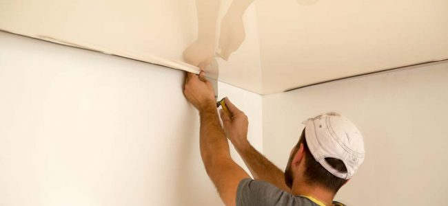 Man installeert spanplafond.