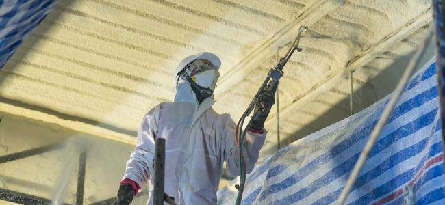 Man in beschermend pak is bezig met het isoleren van de kelder.