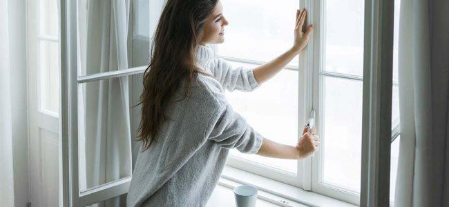 Vrouw die ramen sluit.
