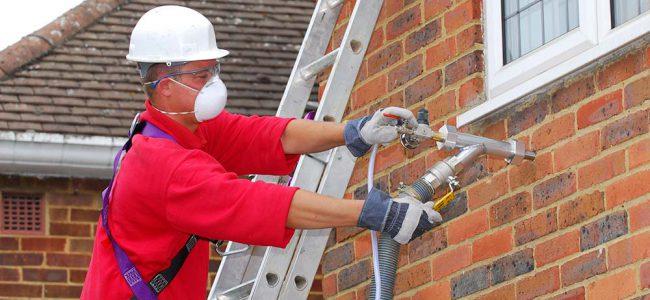 Een man op een ladder met een masker brengt spouwmuurisolatie aan.