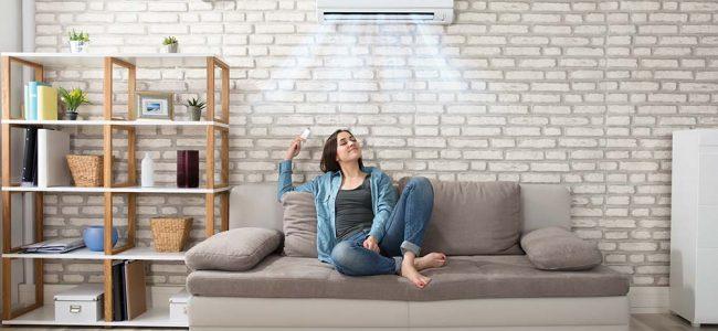 Vrouw in een bruine zetel die geniet van de airco