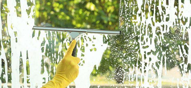 Persoon met gele handschoen die ramen aan het kuisen is